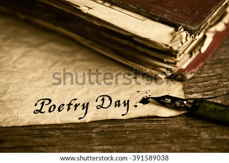 closeup of an old book, an old dip pen and a yellowish paper with the text poetry day written with black ink in it, on a rustic wooden table - stock photo