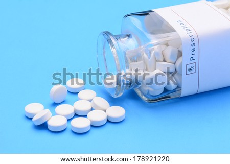Closeup of an old fashioned medicine bottle laying on its side with pills spilling out. Horizontal format on a blue background. - stock photo