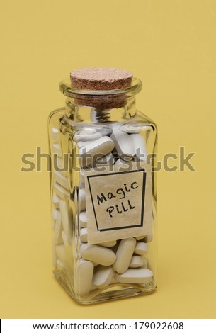 Closeup of an old fashioned pill bottle filled with Magic Pills. The Clear Glass bottle has a label with the words Magic Pill. Vertical format on a pale yellow background. - stock photo
