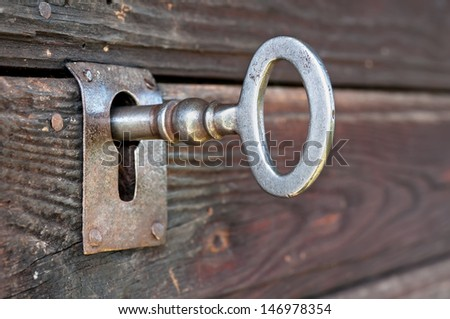 Closeup of an old keyhole with key - stock photo