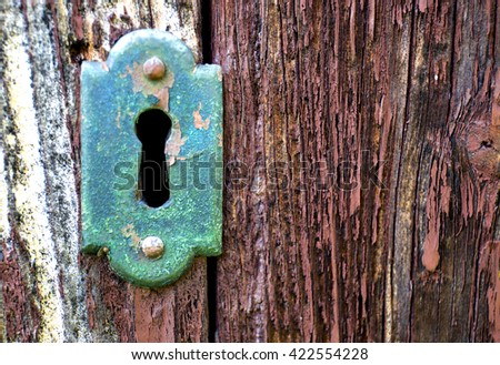 Closeup of an old keyhole with key on a wooden antique door.