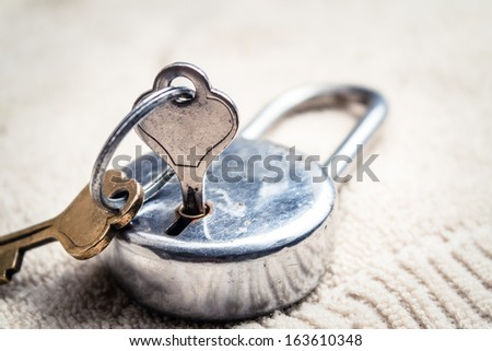 Closeup of an old pad lock with keys - stock photo