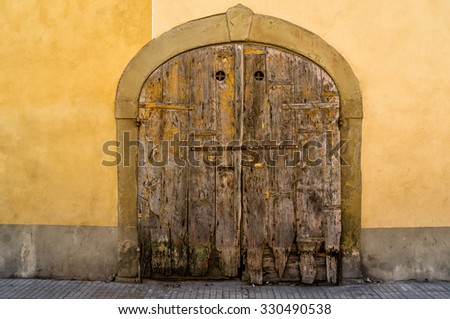 Closeup of an old ramshackle wooden door with shabby yellow walls. Italy. - stock photo