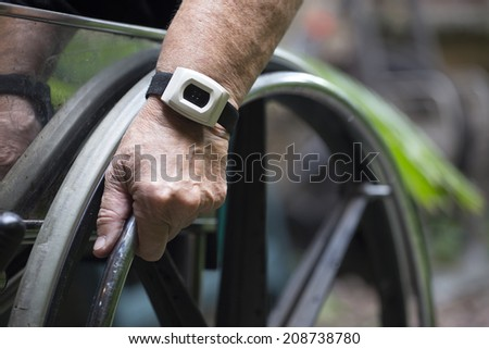 closeup of an old woman hand on a wheelchair - stock photo