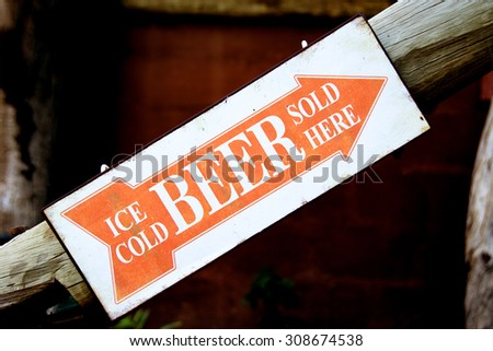 Closeup of an Orange and White Sign indicating the Direction to the Bar, Upstairs - Ice Cold Beer Sold Here - stock photo