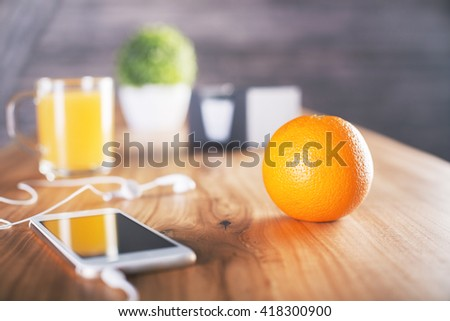 Closeup of an orange on wooden desktop with smartphone and headphones, cup with juice and other items - stock photo