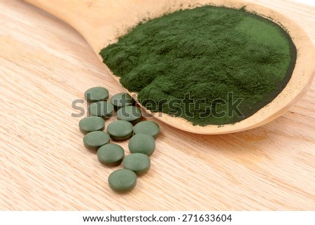 Closeup of an organic Spirulina algae powder and pills in a wooden spoon