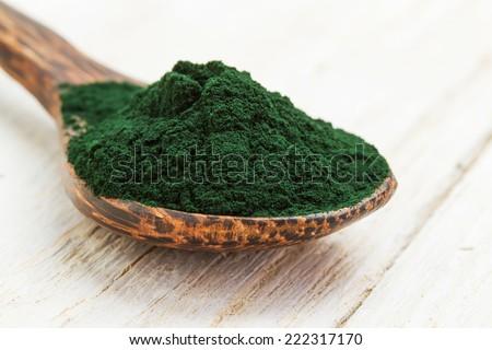 Closeup of an organic spirulina algae powder in a wooden spoon - stock photo