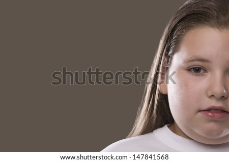 Closeup of an overweight serious girl against gray background - stock photo