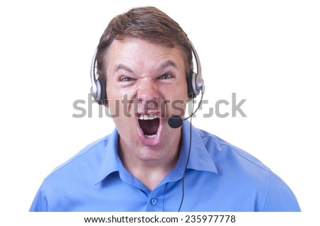 Closeup of angry Caucasian male customer service representative wearing blue collar shirt and communications headset looking at camera and yelling furiously  - stock photo