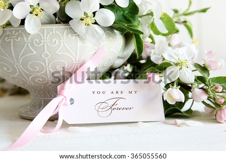 Closeup of apple blossom flowers in vase with gift card
