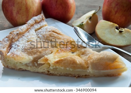 closeup of apple pie with raw apples on wooden table - stock photo