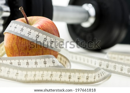 Closeup of apple wrapped with measuring tape and weights in background. Conceptual of fitness and dieting. - stock photo