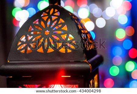 Closeup of Arabic lantern from top view with colorful out of focus lights. Ramadan and Eid concept.