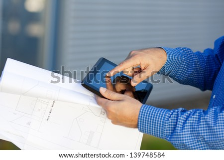 Closeup of architect's hands holding blueprint while using digital tablet - stock photo
