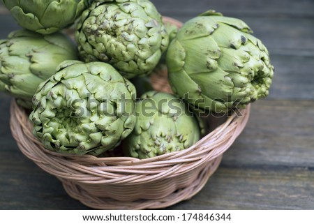 closeup of artichokes in a tray on a rustic wooden table - stock photo