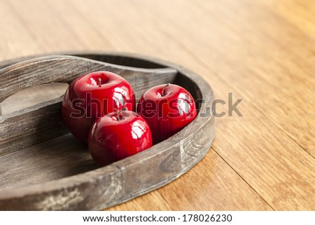 Closeup of artificial apples on wooden tray with shallow depth of field. - stock photo