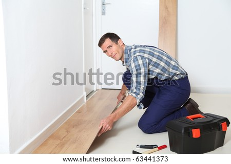 Closeup of artisan installing flooring in room