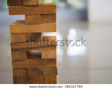 Closeup of asian kid's hand playing wood blocks stack game (jenga) - stock photo