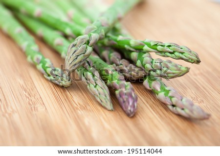Closeup of asparagus on bamboo chopping board - stock photo