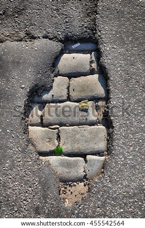 Closeup of asphalt in the street revealing old cobble stones. - stock photo