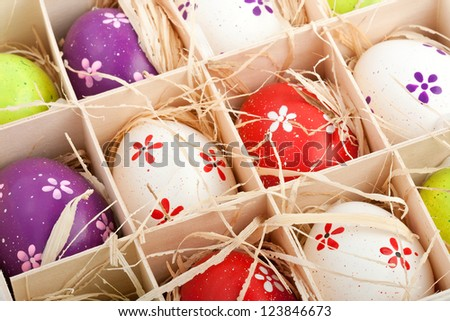 closeup of assorted colorful painted easter eggs in a wooden box