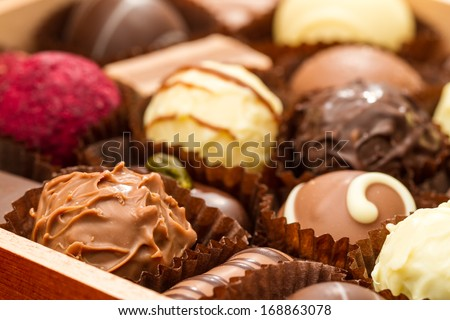 Closeup of assorted praline chocolates in open box or tray. - stock photo