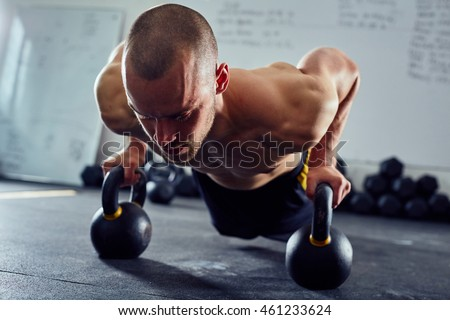 Closeup of athletic man doing kettlebell pushup exercise at the gym