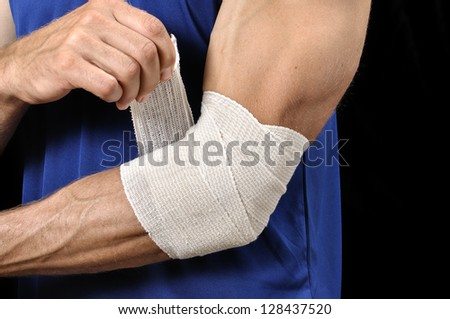Closeup of athletic man tending injured elbow with sports wrap on black background - stock photo
