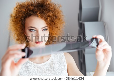 Closeup of attractive curly young female photographer holding and looking at photographic film  - stock photo