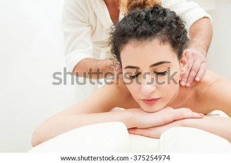 Closeup of attractive woman with fresh skin getting a relaxing spa massage by a male masseur - stock photo