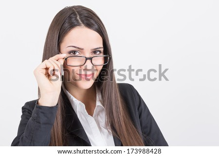 Closeup of attractive young Caucasian brunette real businesswoman wearing eyeglasses looking at camera smiling. Eye vision and business concepts.
