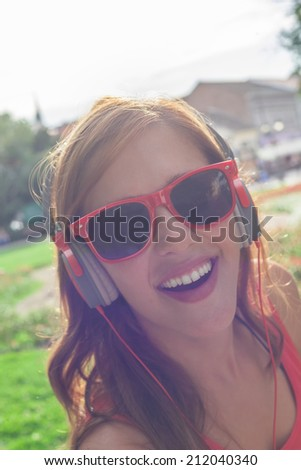 Closeup Of Attractive Young Woman With Headphones Listening To Music Outdoors - stock photo