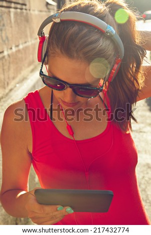 Closeup Of Attractive Young Woman With Headphones Listening To Music Via Digital Tablet - stock photo