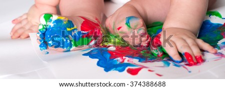 Closeup of baby child hands and feet. Child draws with colored paints hands, dirty feet.  Selective focus. - stock photo