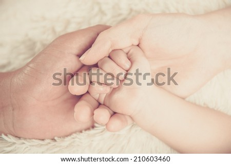 Closeup of baby hand into parents hands. Family concept - stock photo