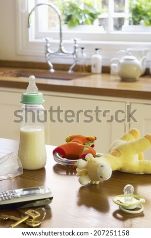 Closeup of baby Items on kitchen counter by cellphone and keys - stock photo