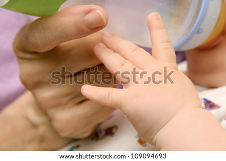 Closeup of baby's and grandmother's hands while the infant drinks from a bottle