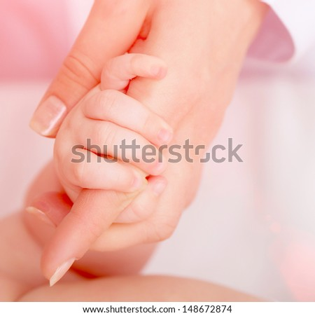 Closeup of baby's hand holding mother's finger