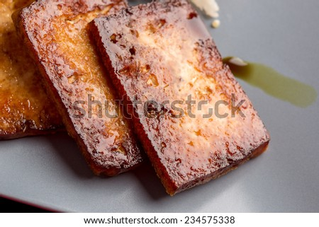 Closeup of backed marinated tofu with soy sauce on a blue plate. - stock photo