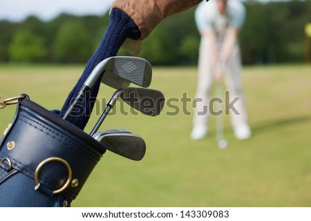 Closeup of bag with golf clubs and man playing in background