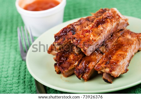 Closeup of barbecued pork ribs on a plate - stock photo