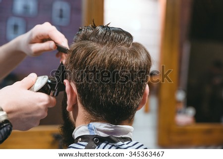Closeup of barbers hands making short haircut to man using trimmer in barbershop