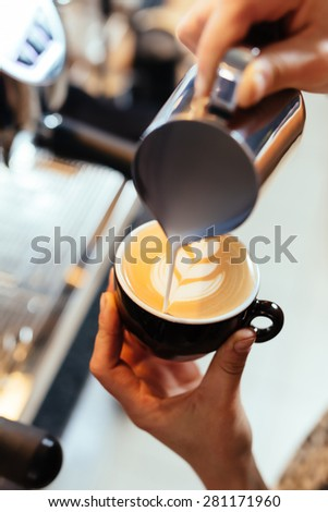 Closeup of barista pouring milk into art cappuccino or latte - stock photo