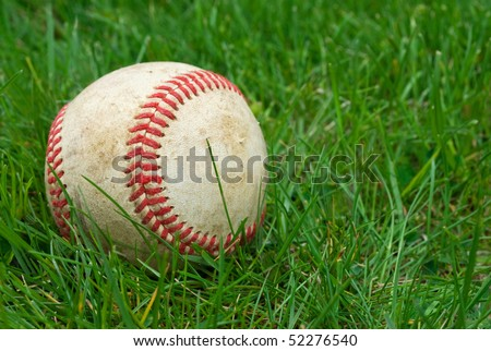 closeup of baseball in the grass, shallow depth of field with focus on ball, copy space at right - stock photo