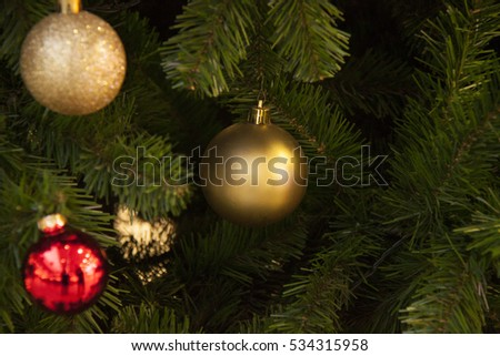 Closeup of baubles hanging from a decorated Christmas tree.