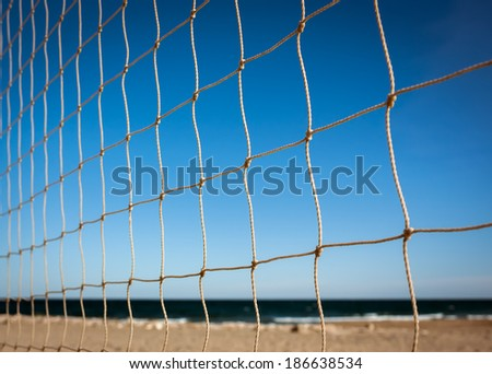 Closeup of beach volleyball net at sunset - stock photo