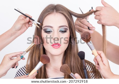 closeup of beautiful blond girl getting makeup done by many hands isolated over white - stock photo
