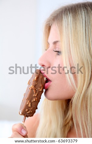 Closeup of beautiful blond woman eating ice cream - stock photo