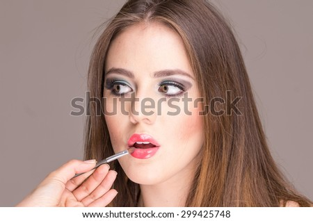 closeup of beautiful blond young woman getting makeup done - stock photo